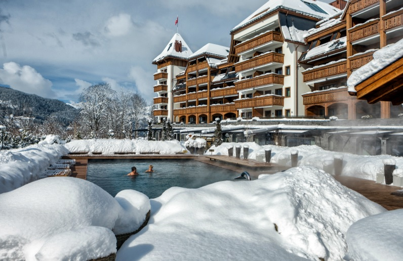 Soak up the stunning scenery from the outdoor swimming pool at The Alpina Gstaad
