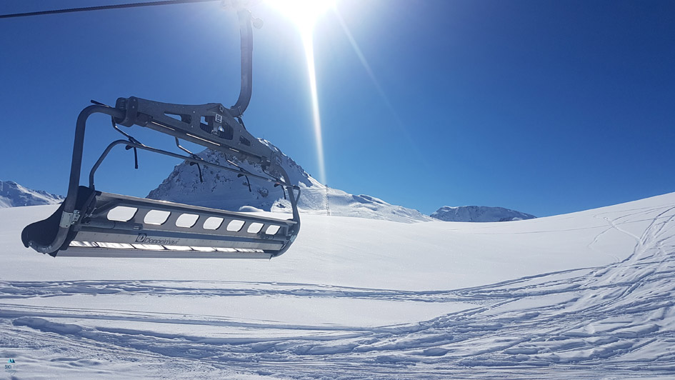 Free Zoom background of a chairlift up the mountain on a bluebird day